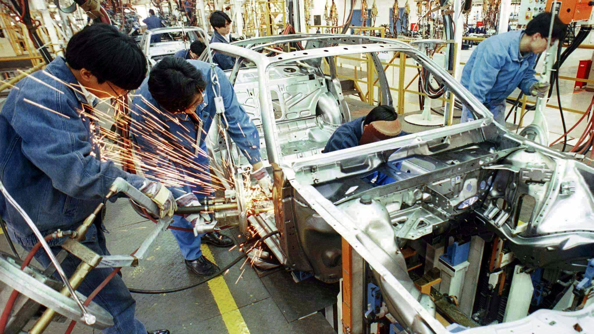 Workers assemble a car at a VW factory in China