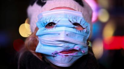 An anti-lockdown protester wears face masks across her face in London.