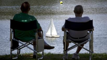 Men sail model boats at a pond in Spanish Springs at the world's largest retirement community
