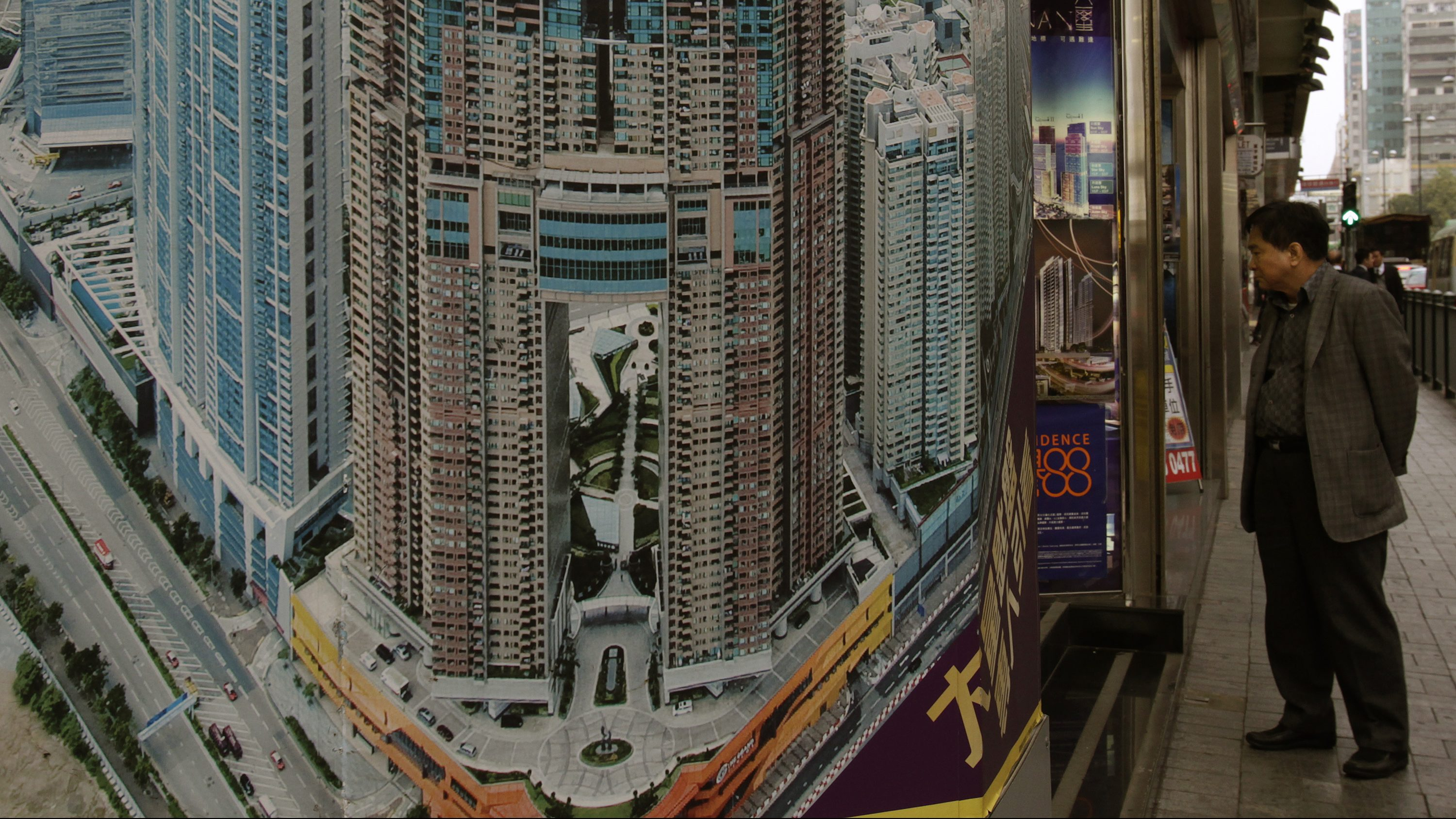 A man checks property prices at a realty agency displaying a photo of The Arch, a luxury high rise apartment, at Hong Kong's West Kowloon district