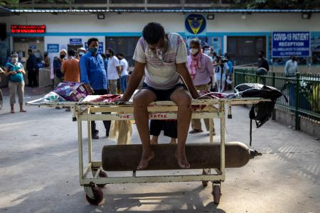 A patient suffering from the coronavirus disease (COVID-19) waits to get admitted outside the casualty ward at Guru Teg Bahadur hospital, amidst the spread of the disease in New Delhi, India.