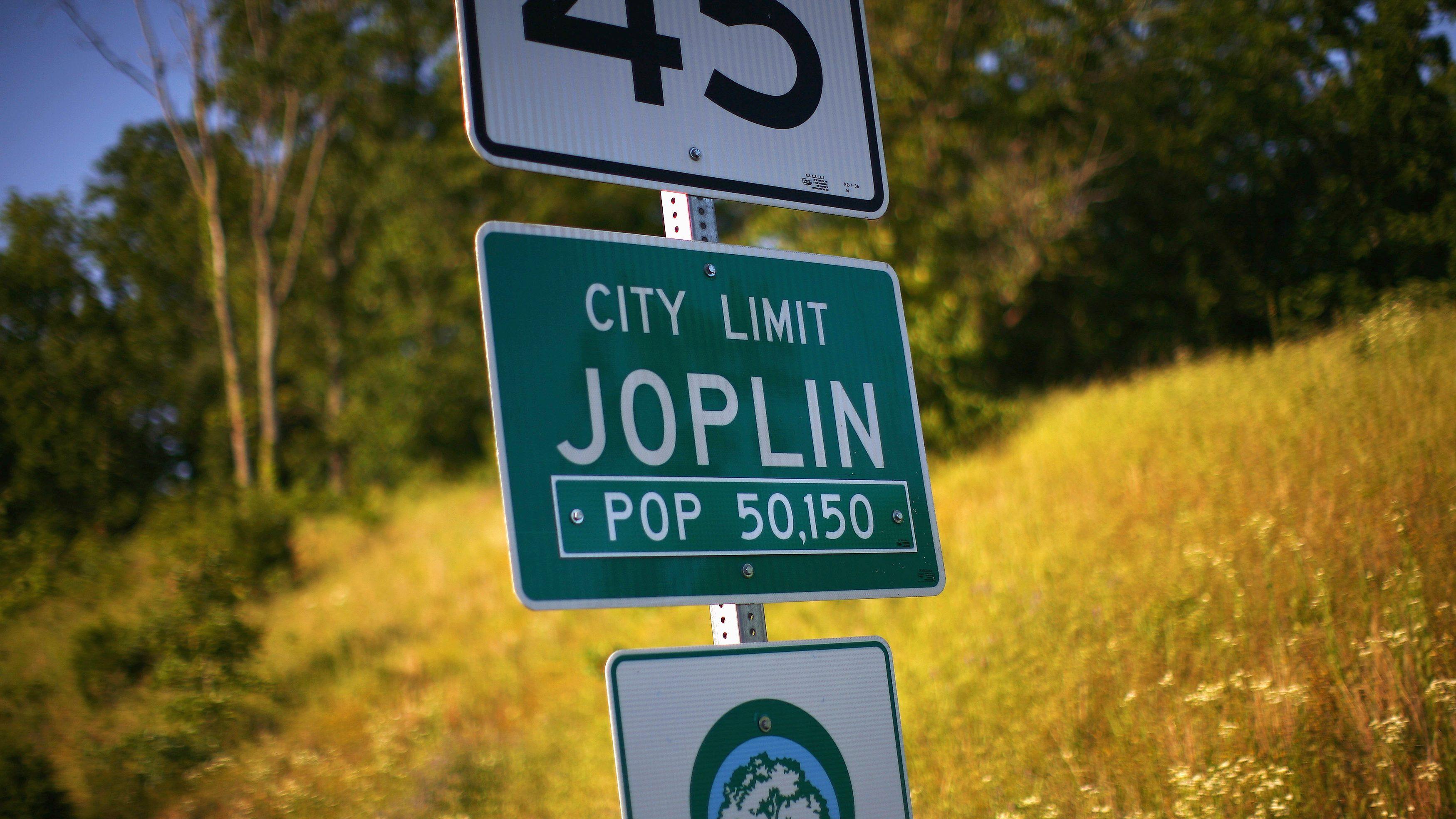"A photograph of a road sign reading ""city limit Joplin, pop 50,150"""