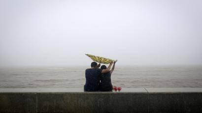 A couple tries to hold on to an umbrella flipped inside out at a sea front, in Mumbai