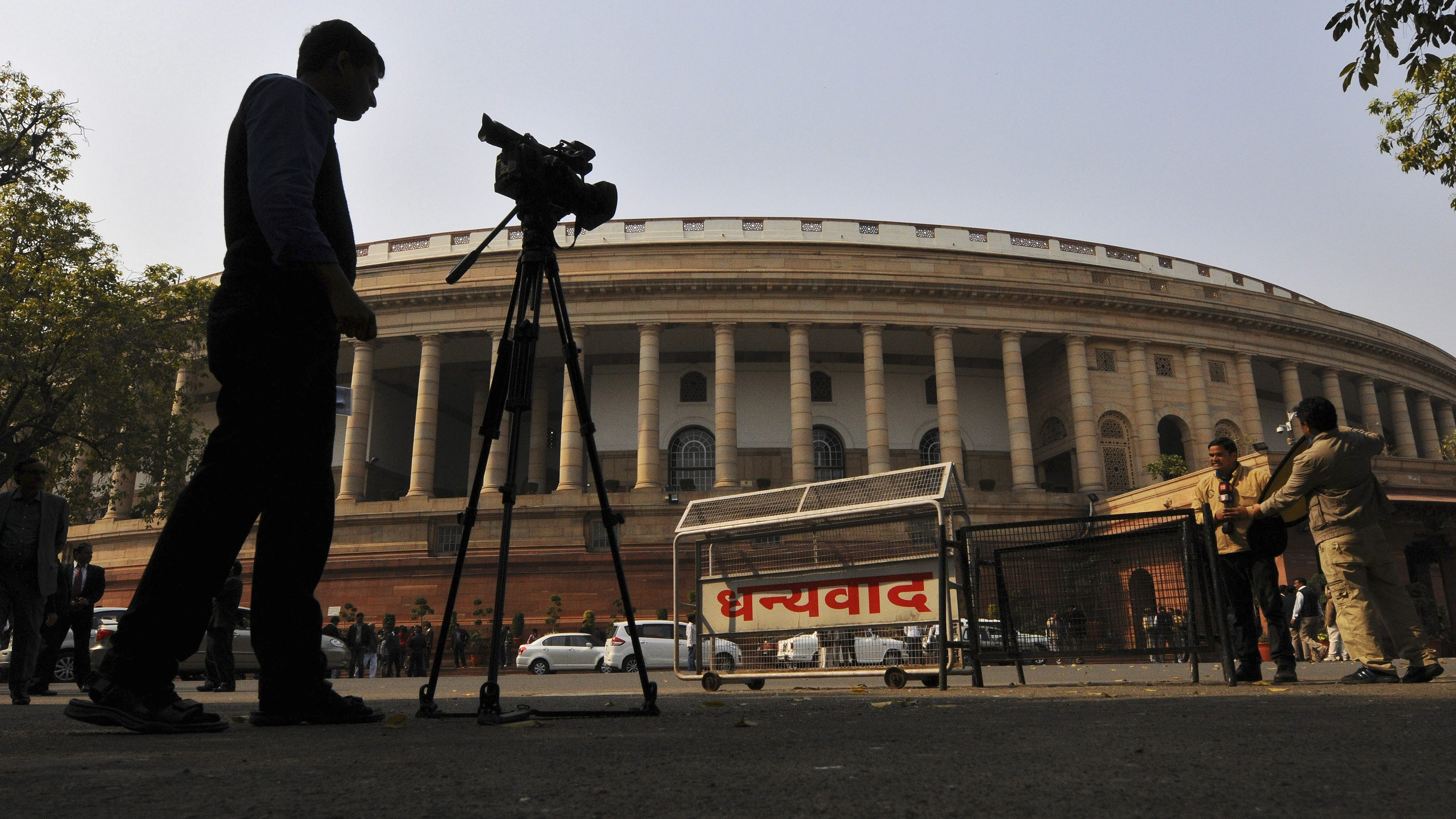 Television journalists report from the premises of India's Parliament in New Delhi