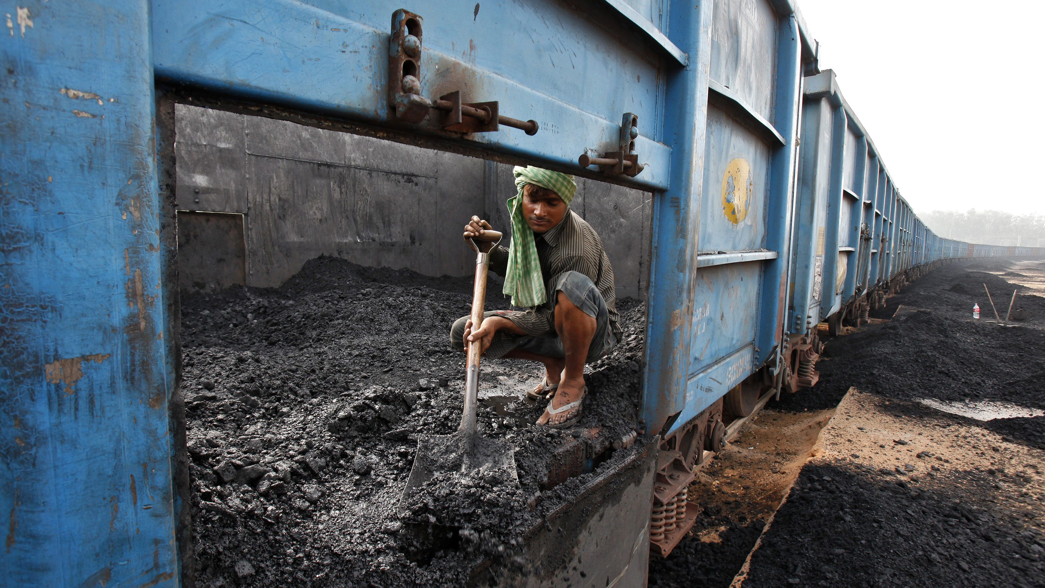 Worker unloads coal from a goods train at a railway yard in Chandigarh