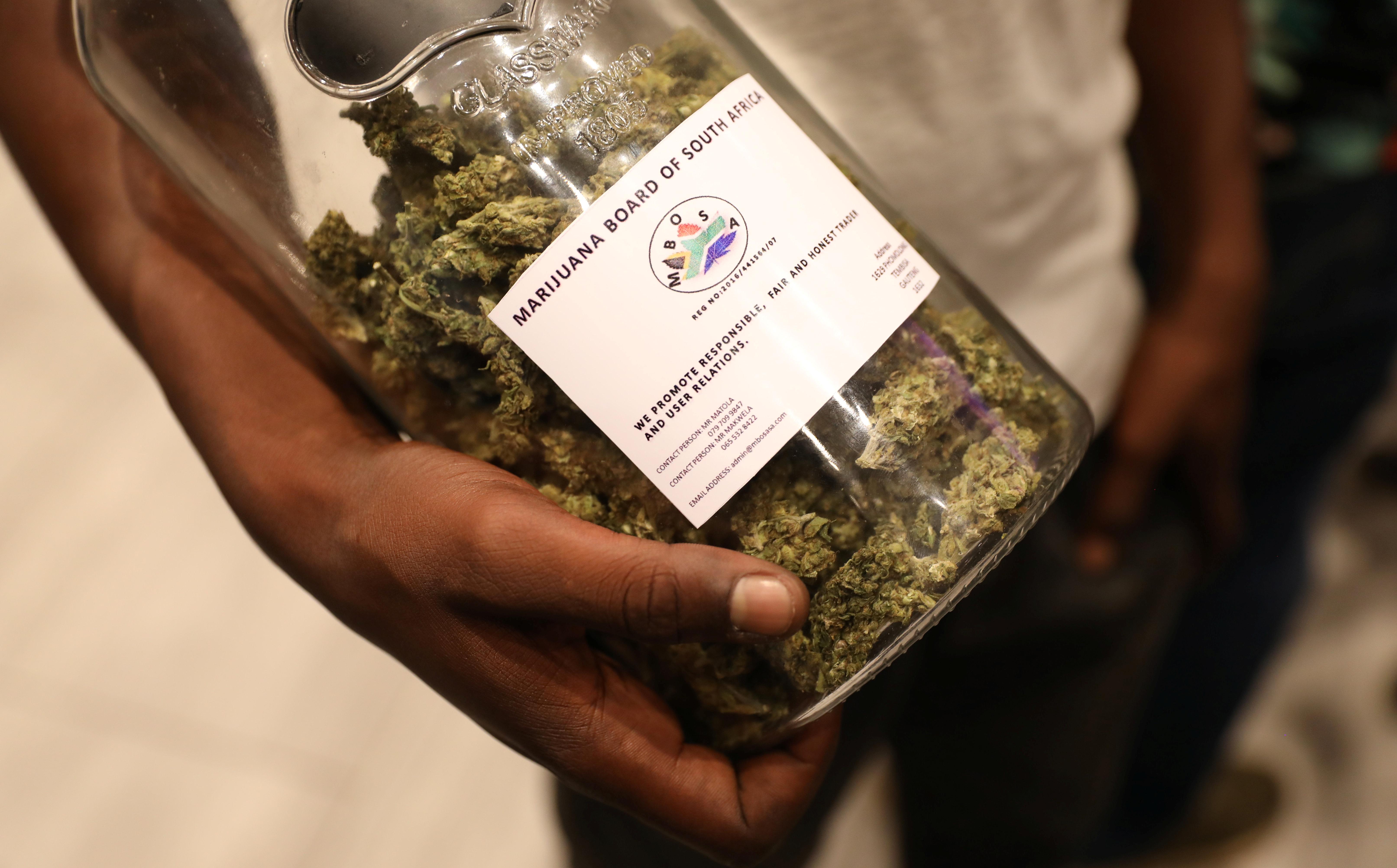 Um homem segura um pote cheio de botões de cannabis em um show de 2018 na África do Sul.