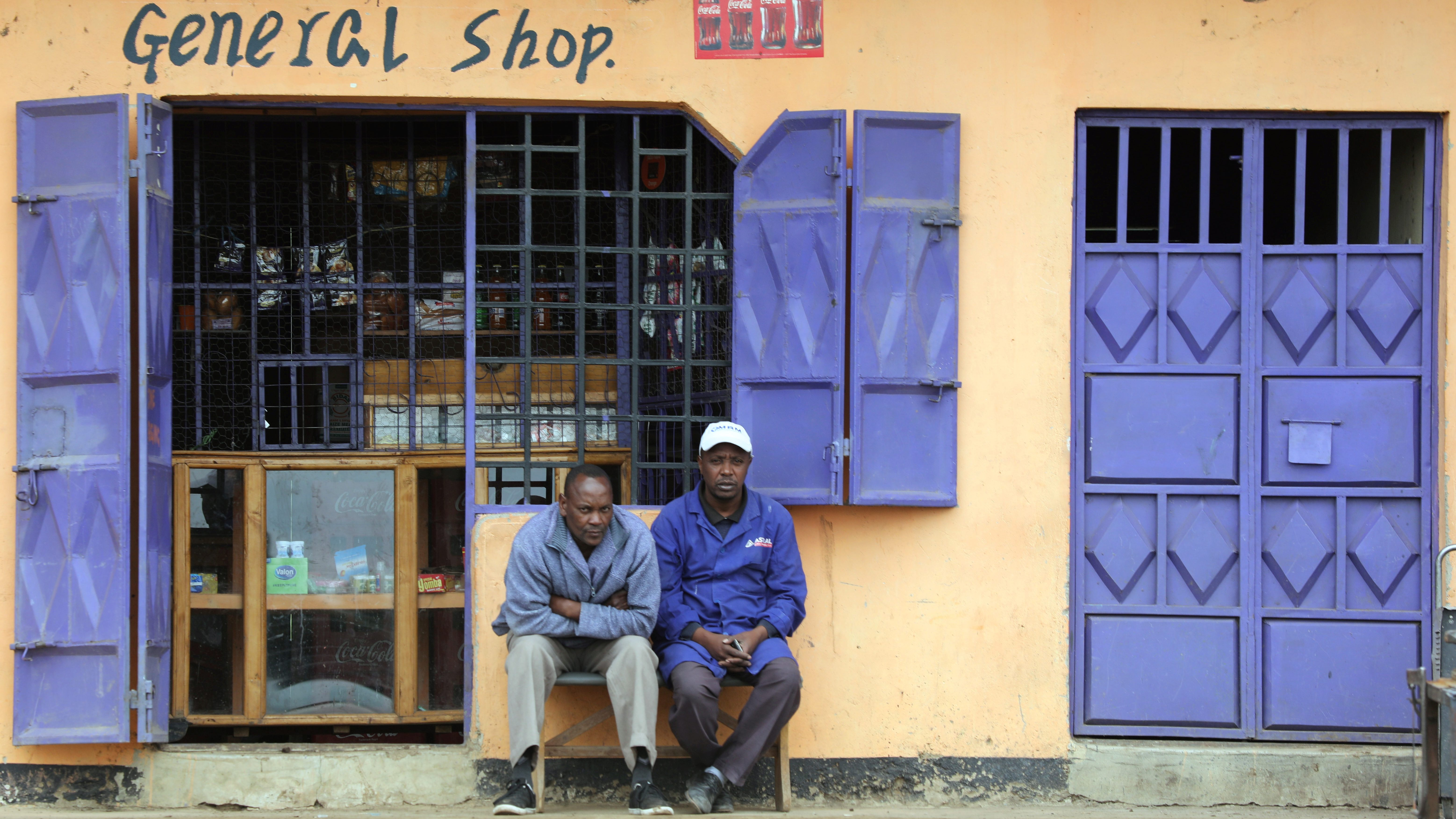 Two men sit in front of a retail shop near Naivasha town in Kenya.