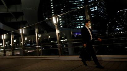 A worker wearing a protective face mask walks past office buildings in the background, during the global outbreak of the coronavirus disease (COVID-19), in Tokyo.