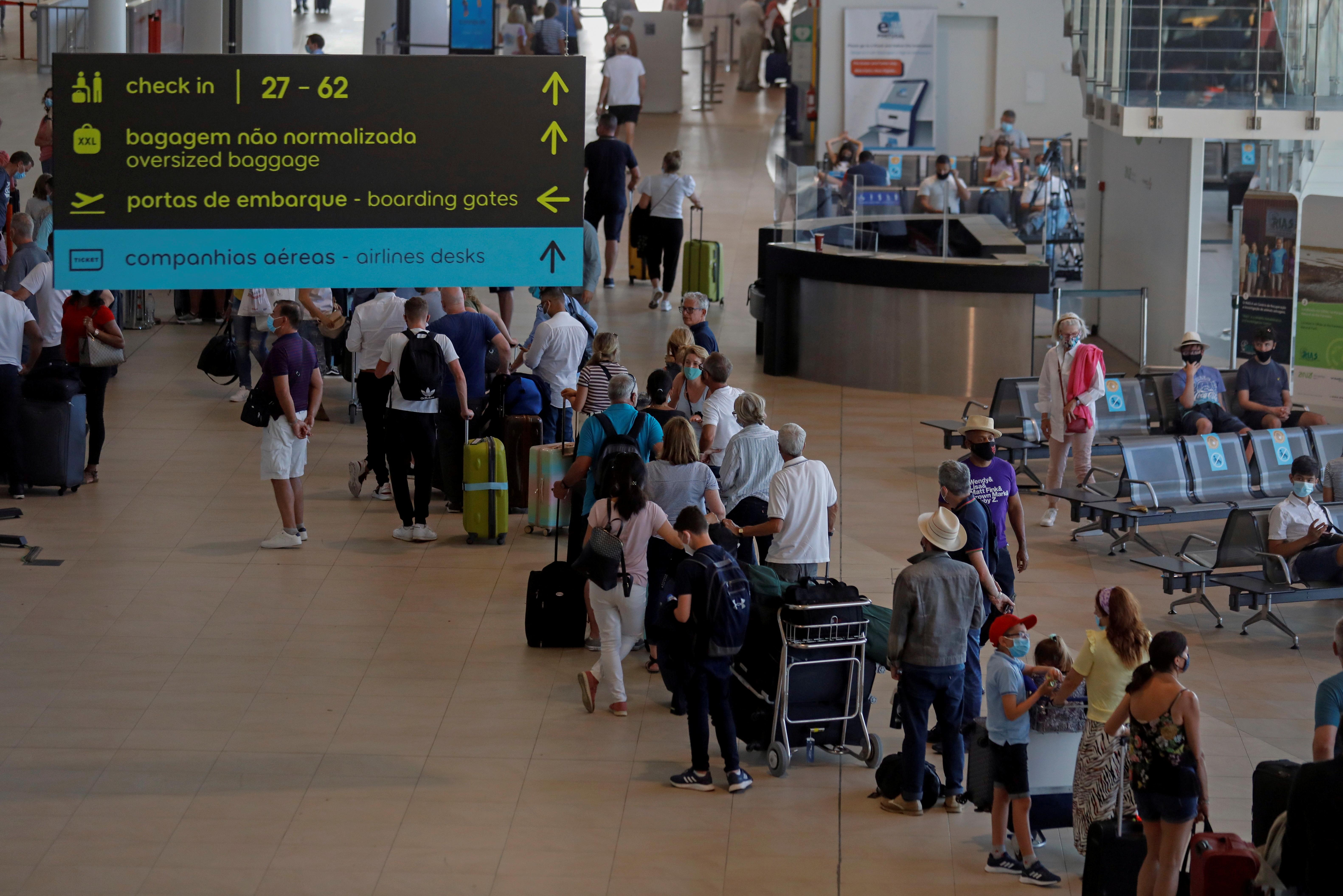 People wait in queues at Faro airport amid the coronavirus disease (COVID-19) pandemic, in Faro