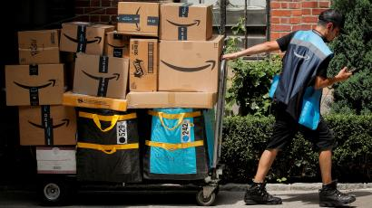 An Amazon delivery worker pulls a delivery cart full of packages during its annual Prime Day promotion in New York City