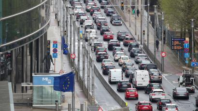 Many cars on a road next to a building and an EU flag in Brussels, Belgium