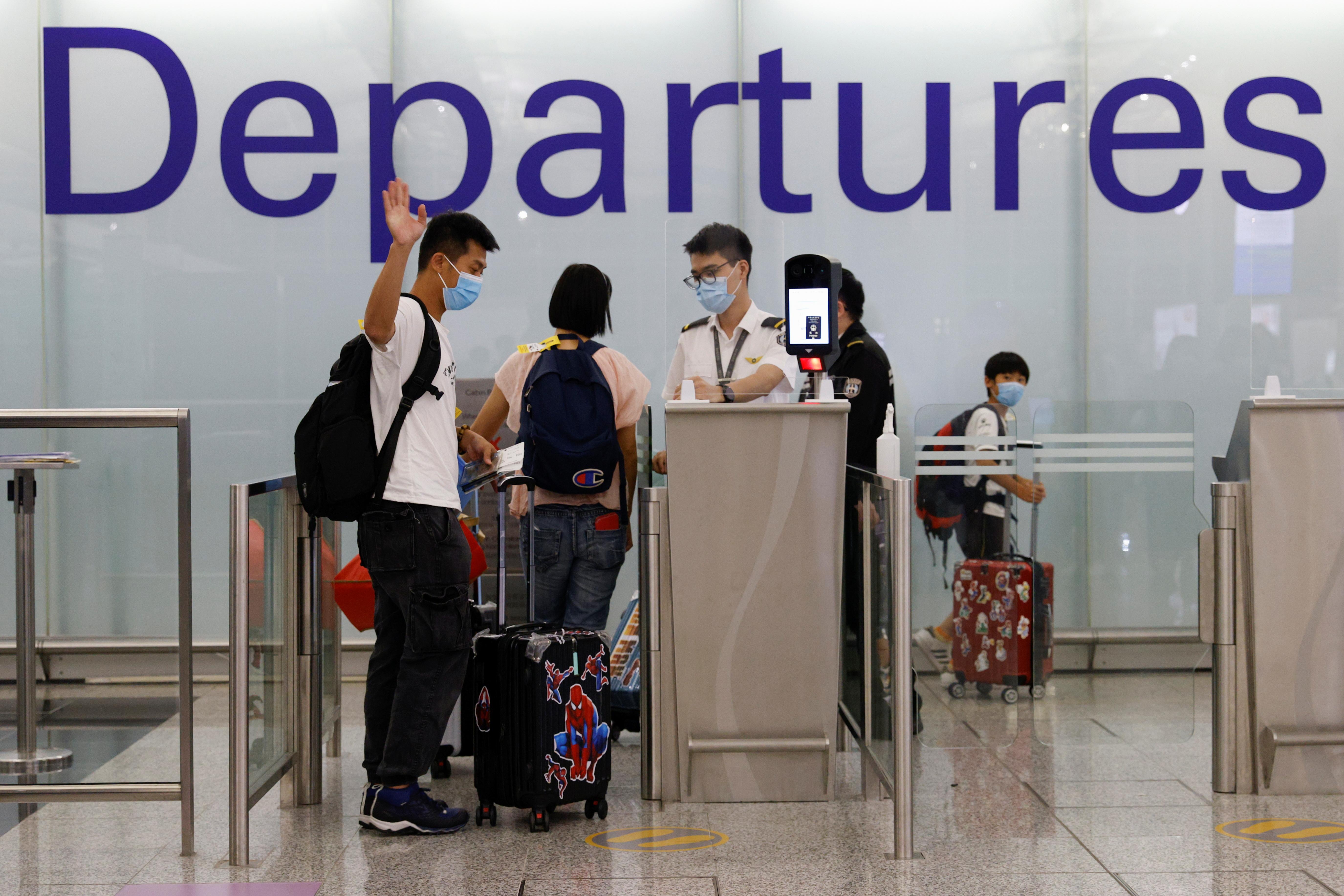 A man waves to his family members before departing to United Kingdom at the Hong Kong International Airport in Hong Kong, China June 30, 2021. REUTERS/Tyrone Siu