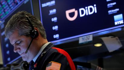 A stock trader with a US flag emblazoned on his sleeve works in front of a screen displaying the logo for Chinese ride-hailing app Didi on the floor of the New York Stock Exchange.