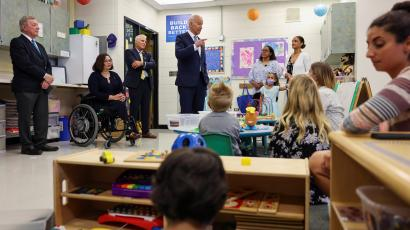 Senator Tammy Duckworth, seated in a wheelchair, President Joe Biden, and one other man, Clint Gabbard, stand in front of a classroom of children.