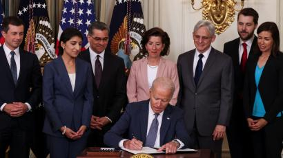 U.S. President Joe Biden signs an executive order flanked by members of his cabinet and American flags.