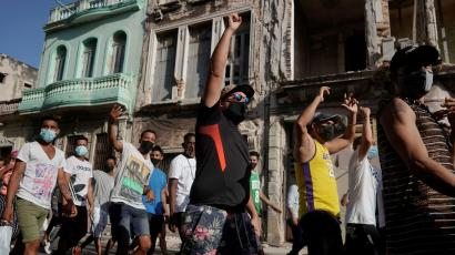 Cuban protesters walk with their fists raised past the colorful and crumbling facades of buildings in Havana.