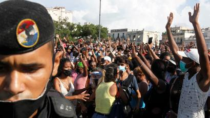 A man in a black uniform and black beret stands in front of a crowd of protesters with their hands up in Havana.
