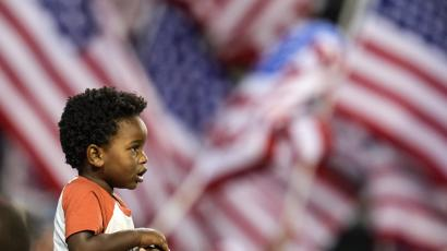 A child stands in front of multiple US flags
