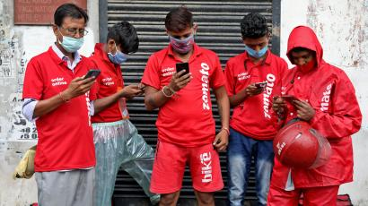 Delivery workers of Zomato wait to collect orders outside a restaurant in Kolkata
