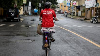 A delivery worker of Zomato rides her bicycle along a road in Kolkata