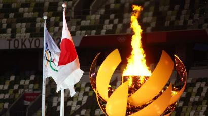 The Olympic flame is seen lit in the cauldron at the opening ceremony alongside a flag of Japan and the Olympic flag