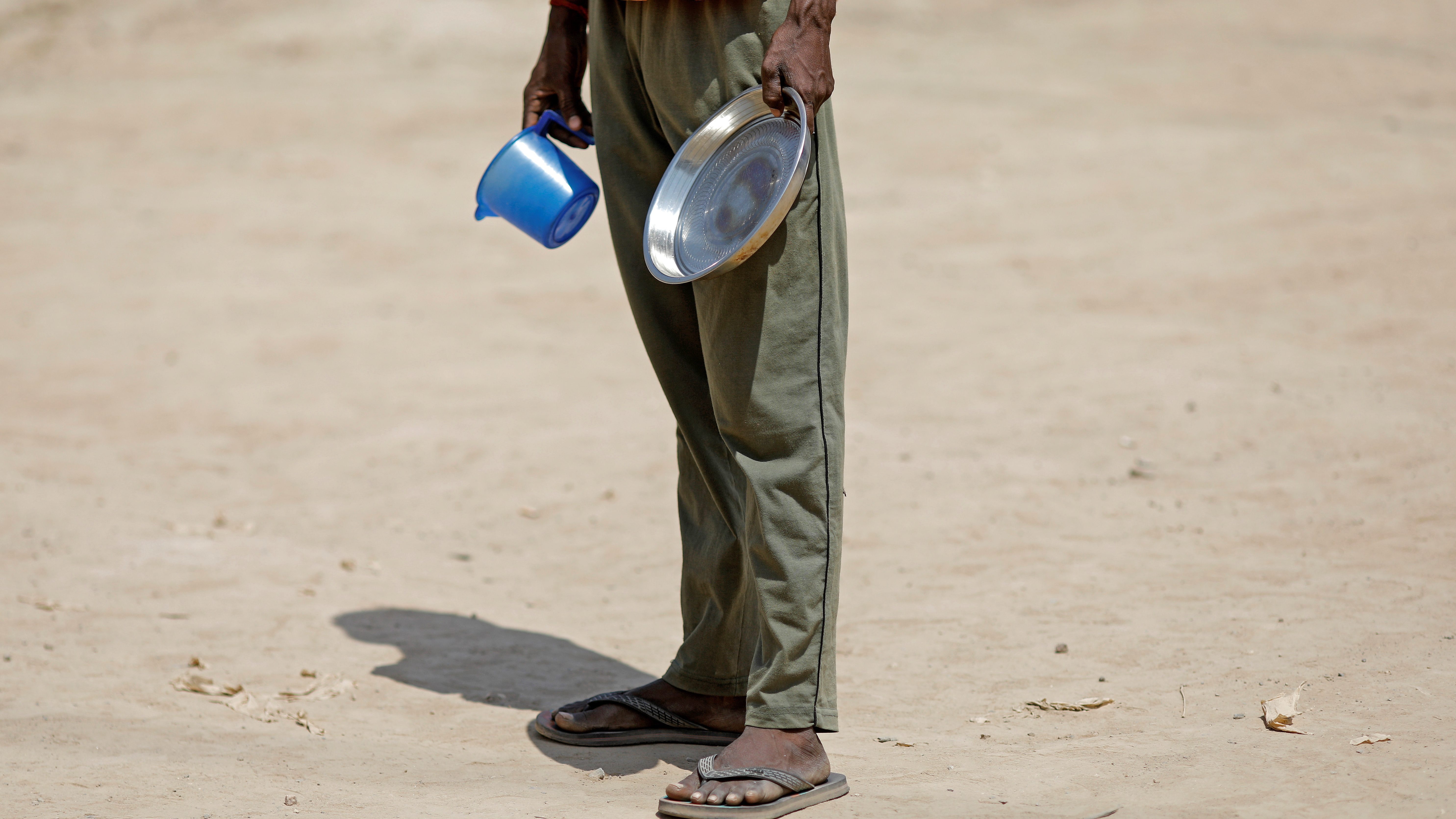 A daily wage labourer waits for free food during a Covid-19 lockdown in Delhi