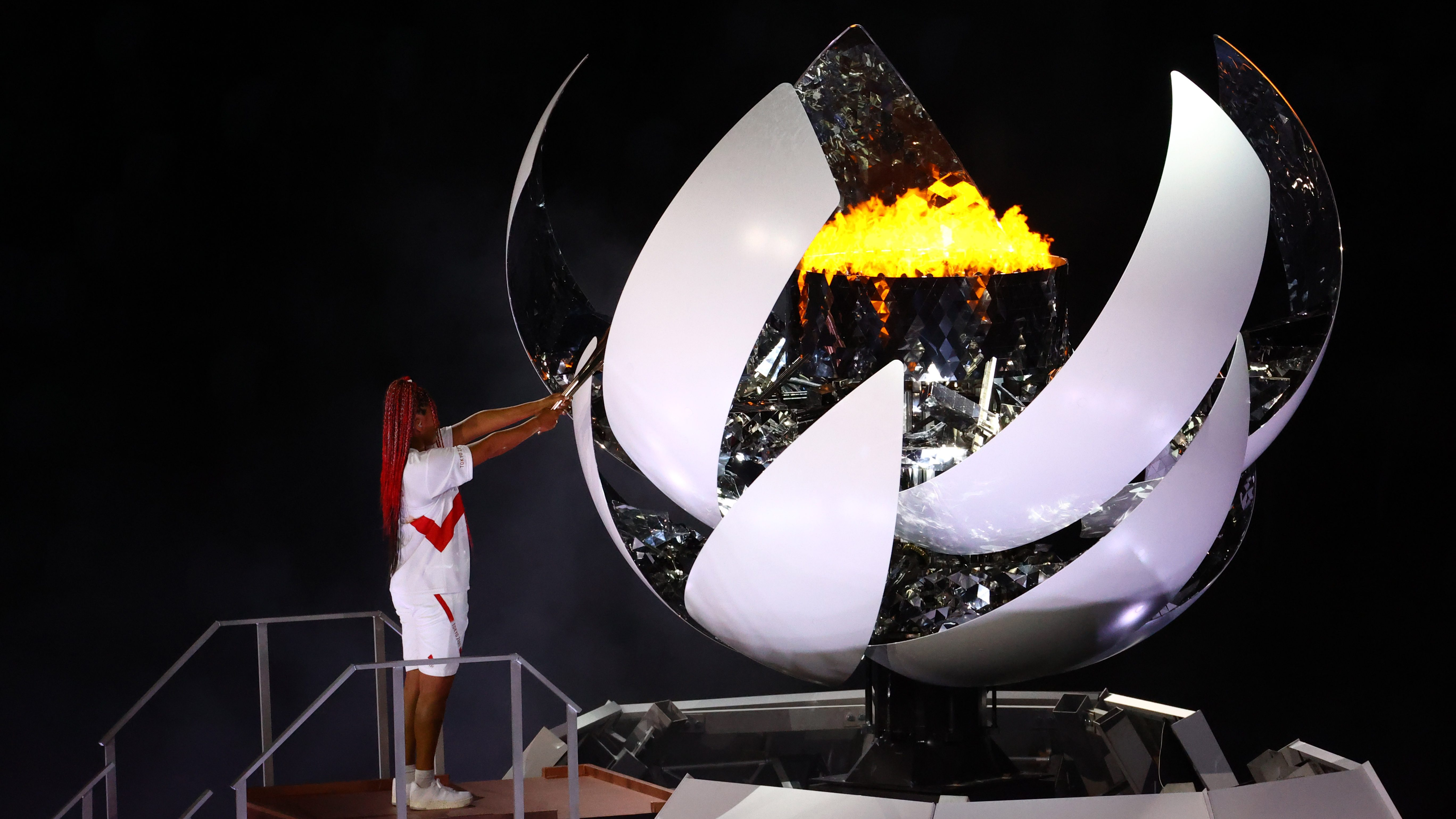 Naomi Osaka of Japan holds the Olympic torch after lighting the Olympic cauldron