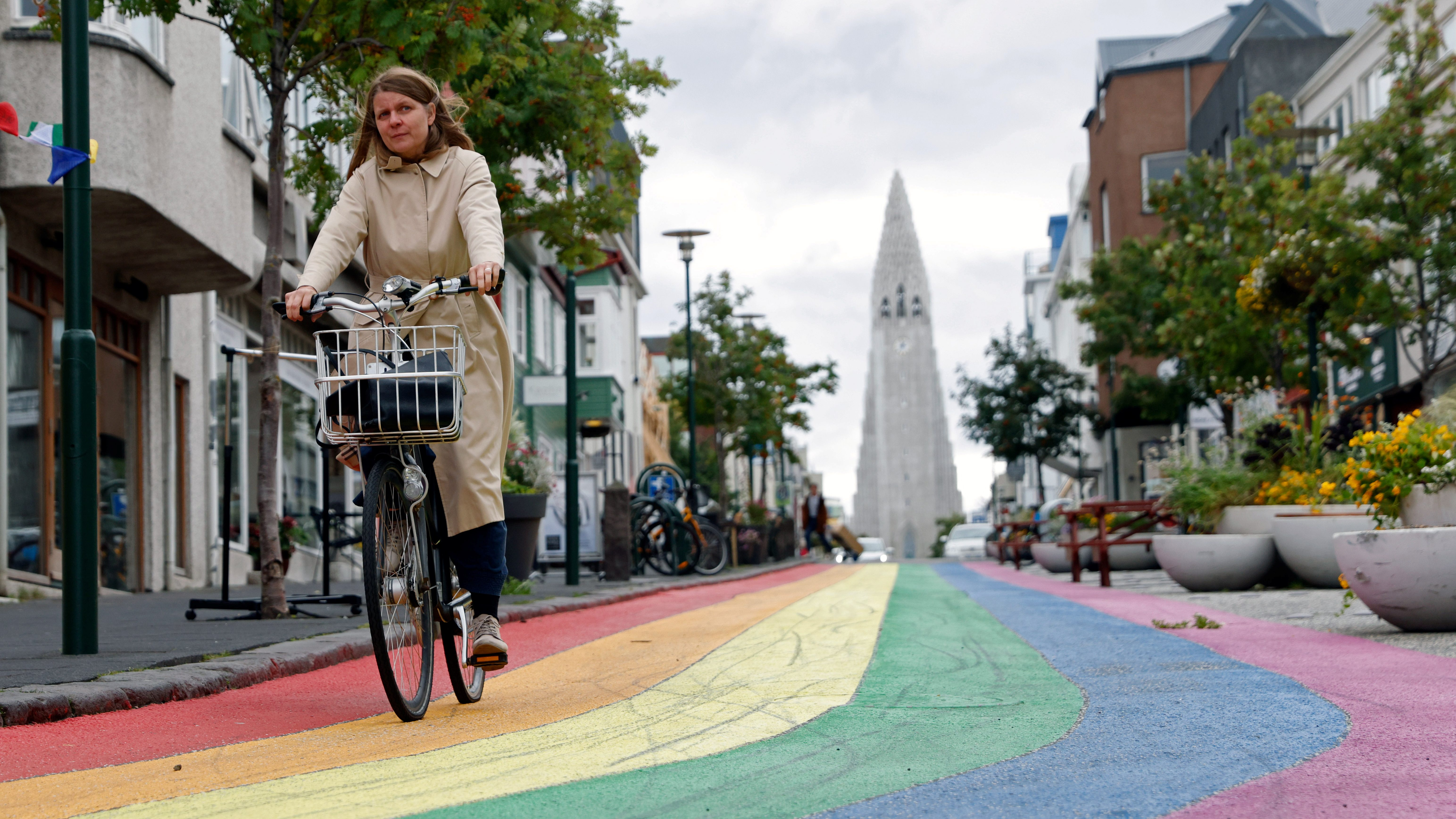 A woman cycles down a street painted in rainbow colours near the Hallgrimskirkja church, as the outbreak of the coronavirus disease (COVID-19) continues, in Reykjavik, Iceland
