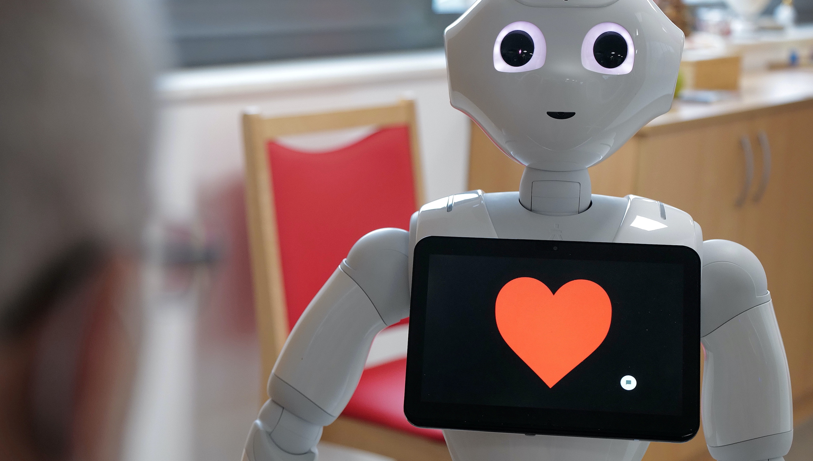 """With a heart on its screen, humanoid robot """"Pepper"""" brightens up the daily life of guests at the day care center of German welfare organization Caritas."""