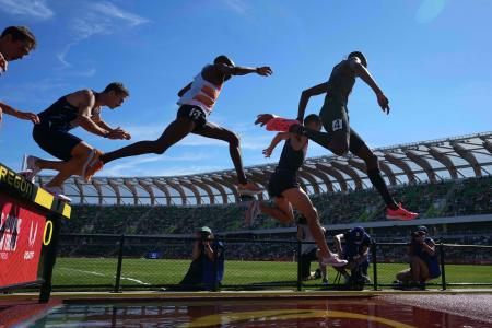 Donn Cabral, Sean McGorty and Hillary Bor race over the water jump in the steeplechase during the US Olympic Team Trials at Hayward Field.