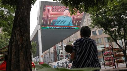 People sit in front of a screen showing Chinese president Xi Jinping speaking