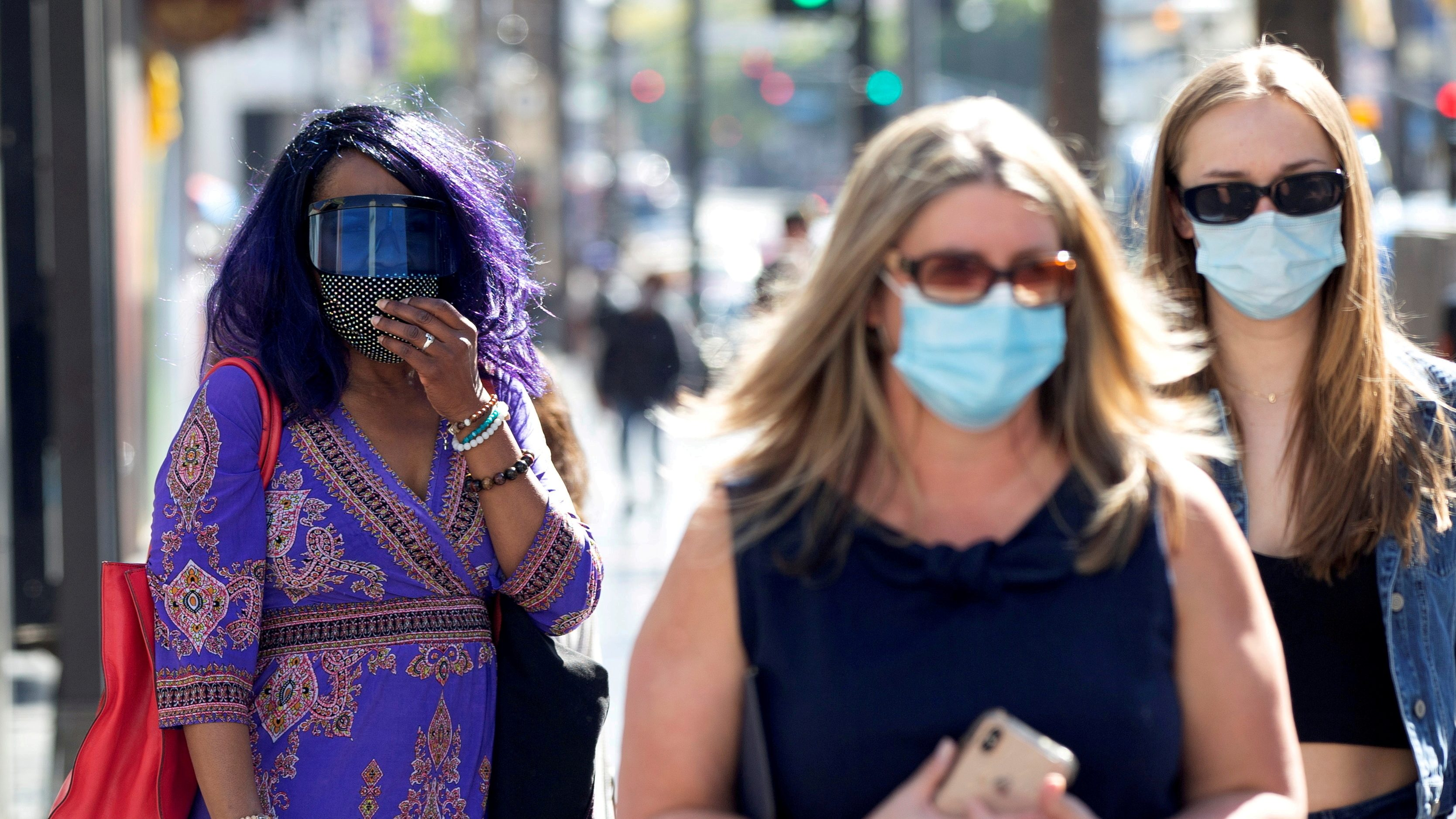 People wearing face protective masks walk on Hollywood Blvd during the outbreak of the coronavirus disease (COVID-19), in Los Angeles