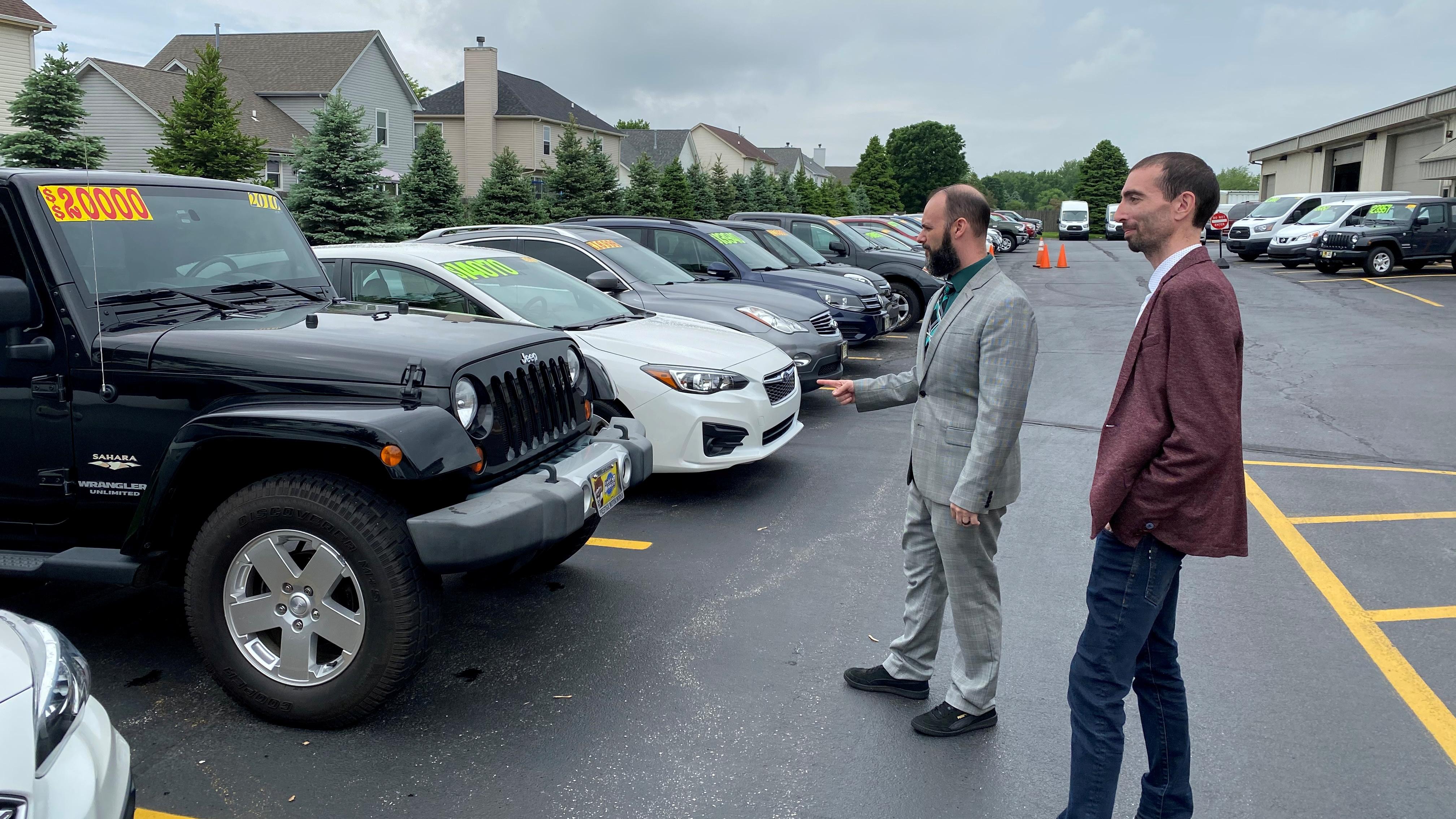 Alex Tovstanovsky, owner of used-car dealer Prestige Motor Works, checks on inventory