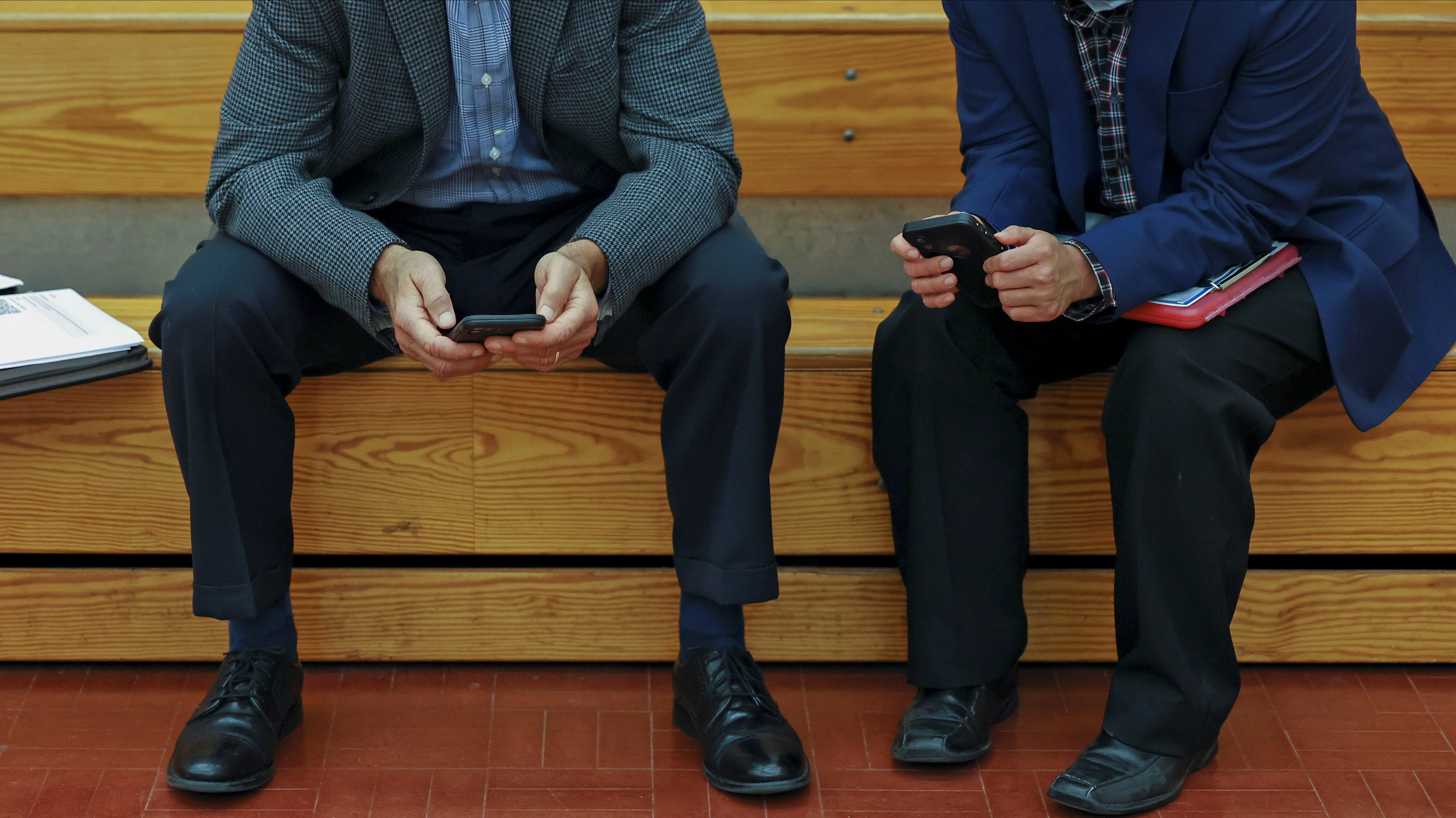 men in suits look at their phones while at a job fair