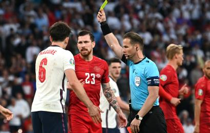 England's Harry Maguire is shown a yellow card by referee Danny Makkelie as Denmark's Pierre-Emile Hojbjerg look on