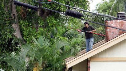 A man trims trees from his roof in anticipation of high winds and rain from Hurricane Wilma