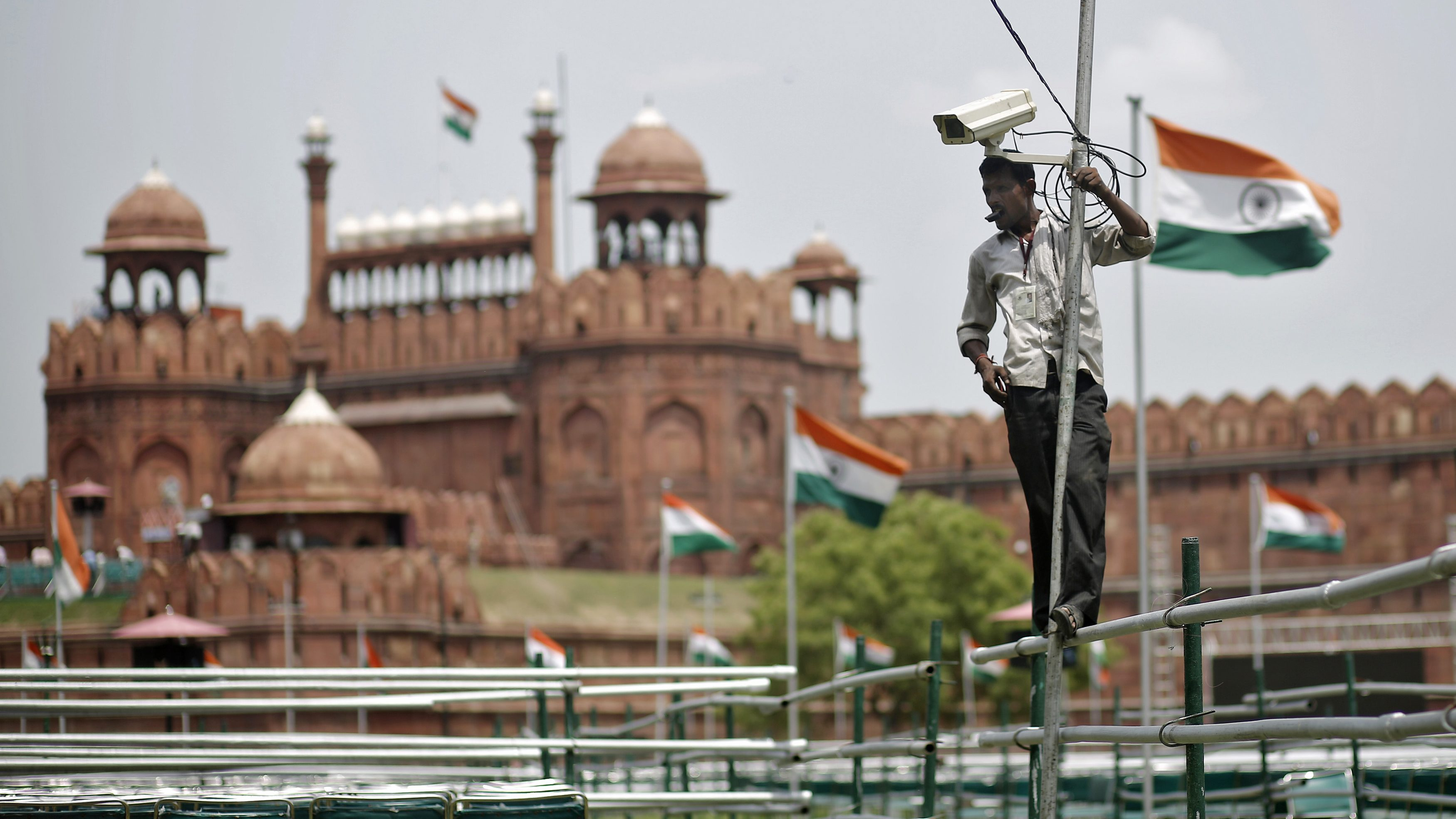 A worker installs a security camera in front of the historic Red Fort on the eve of India's Independence Day celebrations in Delhi
