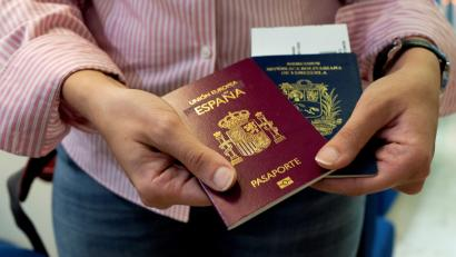 A hand holding two passports
