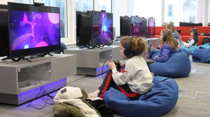 Four girls sit on beanbags in front of computer screens at a camp designed to teach kids how to code video games.
