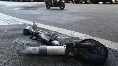 a burned out destroyed piece of a shared scooter lies on a concrete street. A moped can be seen in the background