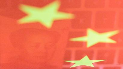A Chinese yuan banknote and a computer keyboard reflected on a Chinese flag.