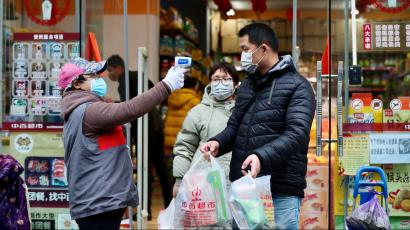 Worker measures body temperature of people leaving a supermarket in Qingshan district following an outbreak of the novel coronavirus in Wuhan