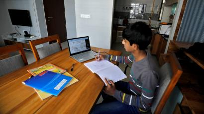 A student makes notes as he attends an online class at his home after Gujarat government ordered the closure of schools and colleges across the state amid coronavirus disease (COVID-19) fears, in Ahmedabad