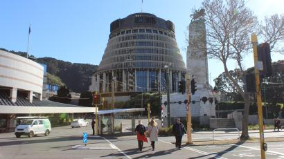 """People walk on a downtown street in front of the executive wing of the New Zealand Parliament complex, known as the """"Beehive"""" because of its shape."""