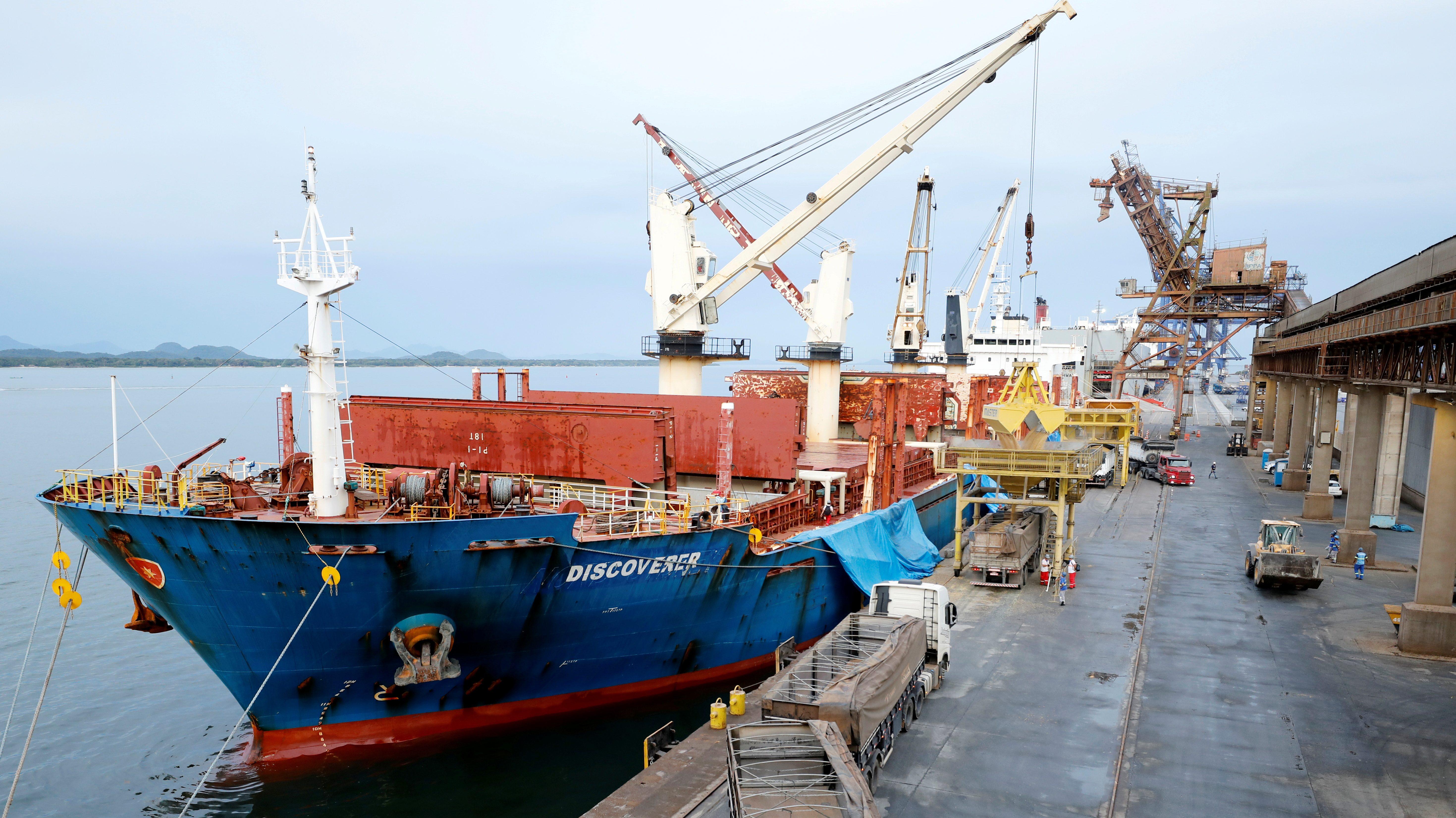An ocean freighter unloads soybeans at a dock.