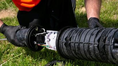 Two gloved hands are shown connecting two ends of aa black tube with cables running through it.