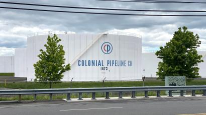 A Colonial Pipeline fuel tank stands against a cloudy sky.