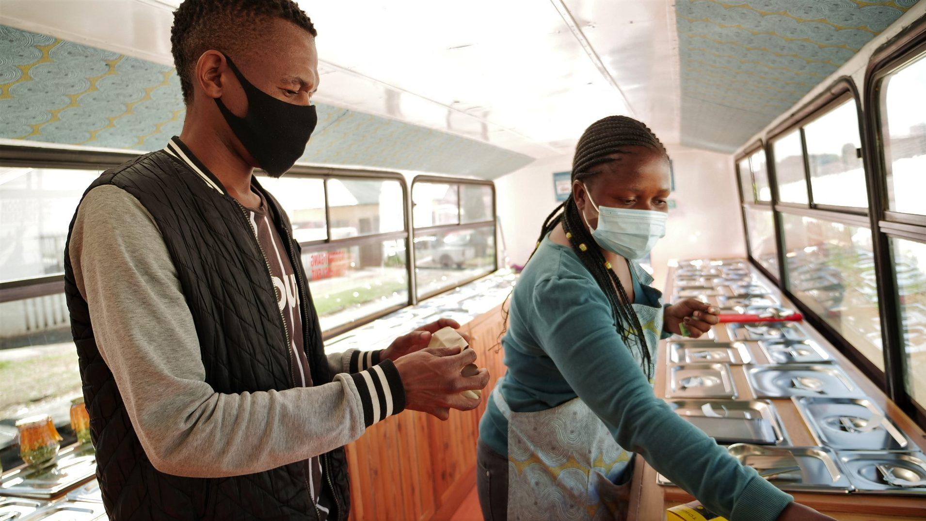 Sanele Msibi assists a customer inside the Skhaftin bus in Johannesburg, South Africa