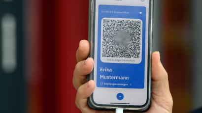 a hand holds an iphone displaying a QR code reading text in German. It is a vaccination certificate