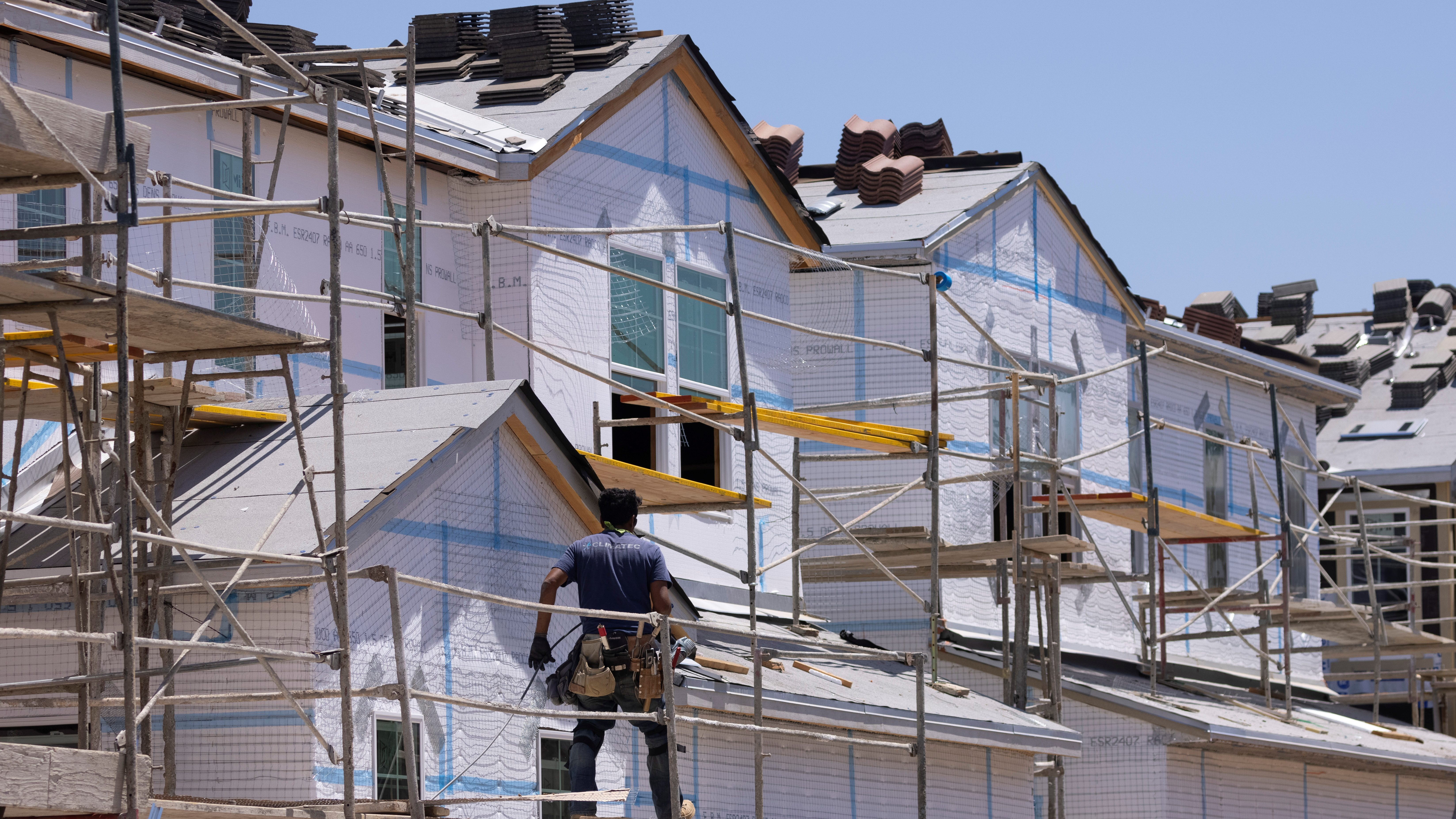 A construction worker stands on scaffolding in front of a house under construction.